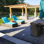 Paver patio with dining table lounge chairs and pergola