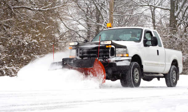 White truck plowing snow and ice