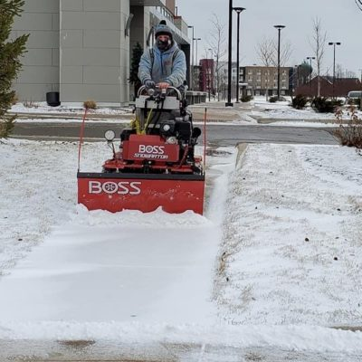 Man clearing snow Land Visions Lansing Michigan