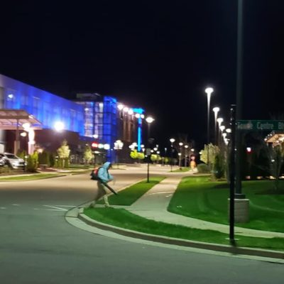 worker blowing off sidewalk at night Land Visions Lansing Michigan
